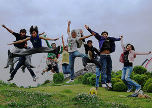 photograph of a group of young adults jumping, caught in midair, on a hill outside