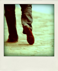 Instant photograph of lower legs and feet walking away. The subject is wearing slacks and brown shoes
